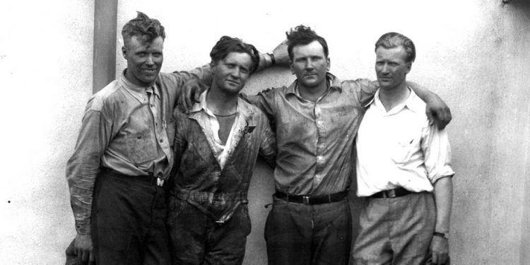 """The """"Four"""" Hunter Bros."""" at Sky Harbor Airport, Northbrook, Ill. Photo taken immediately after landing, July 4th, 1930. Left to righ: Albert, Kenneth, John, Walter"""